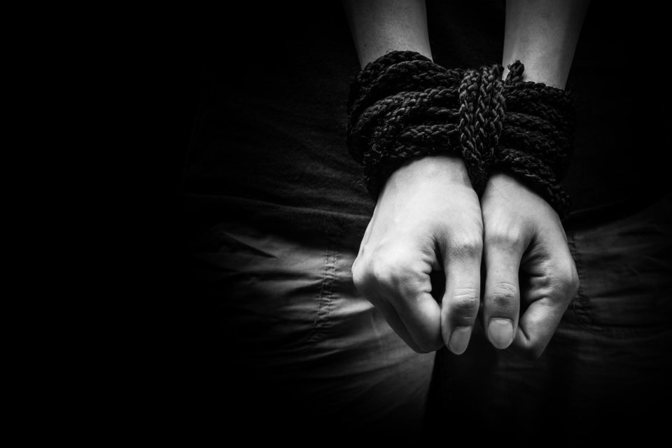 close-up image of a person's hands tied
